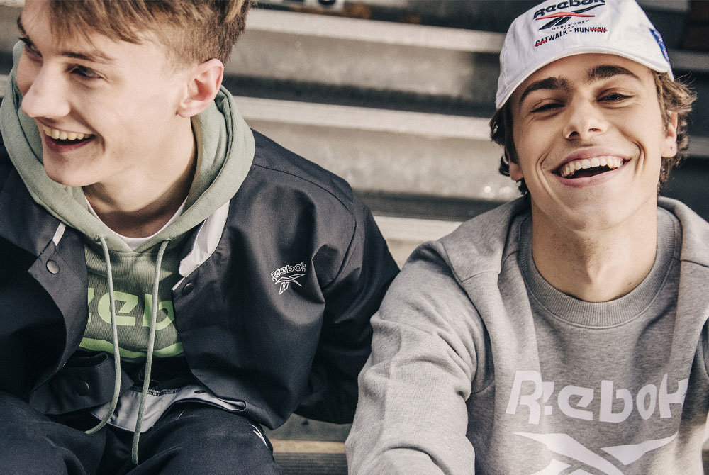 Two young adults sitting in Reebok clothing smiling.