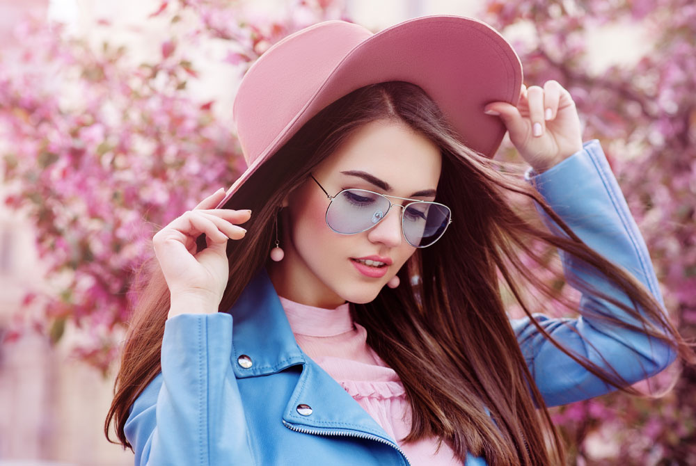 Fashionable girl in a pink hat with oversized glasses.