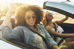 Girls in a convertible driving down the road.