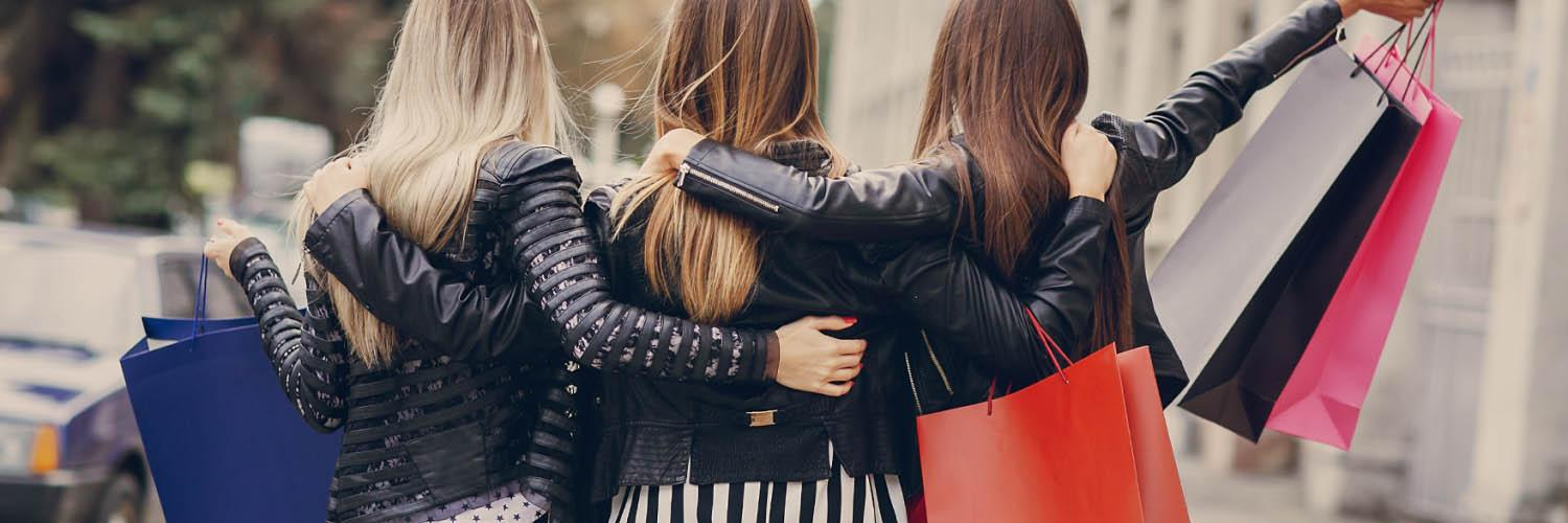 Back view of three friends with shopping bags and arms around each other.